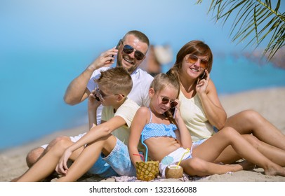 Summer holidays. Family speaking on mobile phone on the beach at the day time.