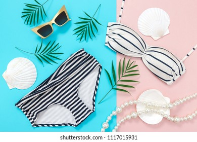 Summer holidays flat lay on blue and pink background. Bikini, sunglasses, palm leaves, pearl necklace and seashells.