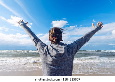 Summer holidays. Girl with her hands up on the sea wearing a sports hoodie