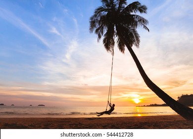 summer holidays, happy woman on the swing on tropical beach at sunset