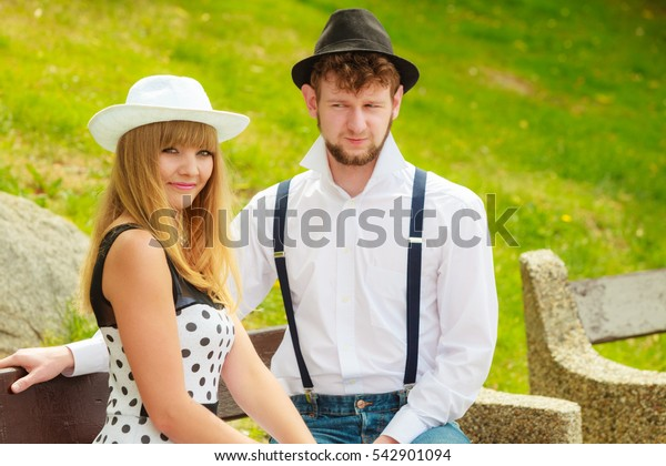 Summer holidays love relationship and dating concept - romantic happy couple retro style sitting on bench in park