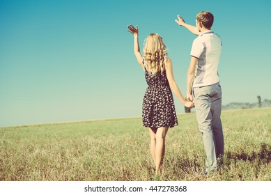 Summer holidays, love, romance and people concept. Happy young hippie couple holding hands and waving to blue sky outdoors from back
