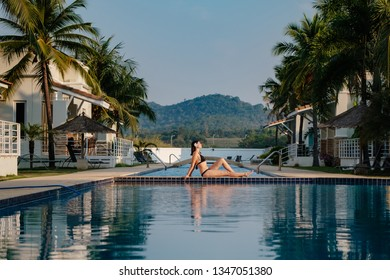 summer holidays in luxury hotel, woman relaxing near beautiful swimming pool. Beauty and body care. Back view, without face