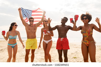 summer, holidays and people concept - group of happy friends with flag and non alcoholic drinks celebrating american independence day and party on beach
