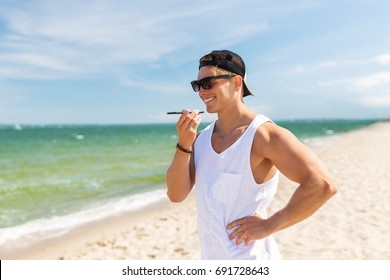 summer holidays and people concept - happy smiling young man in sunglasses using voice command recorder on smartphone on beach
