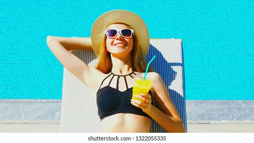 Summer holidays - portrait happy smiling woman with cup of juice on deckchair over blue water pool background