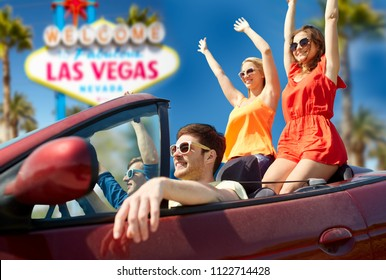 summer holidays, road trip and travel concept - happy friends driving in convertible car and waving hands over welcome to fabulous las vegas sign background
