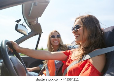 summer holidays, road trip, vacation, travel and people concept - happy young women driving in in cabriolet car and laughing