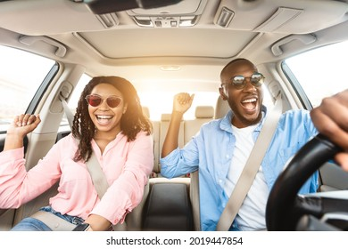 Summer Holidays And Roadtrip Concept. Front view portrait of excited black couple in sunglasses driving car, dancing to music and singing favorite song, going on vacation for rest and relax, sun flare
