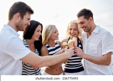 summer, holidays, sea, tourism and people concept - group of smiling friends eating ice cream on beach