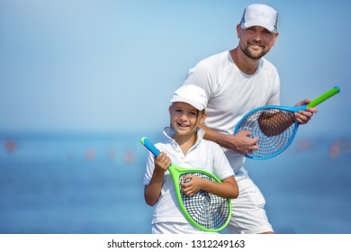Summer holidays. Sport. Lifestyle. Father with daughter playing tennis.