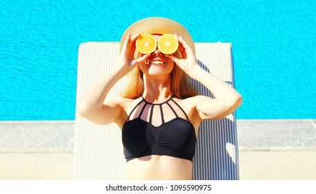 summer holidays - sunny portrait of woman holds in her hands oranges and hides his eyes on blue water pool background