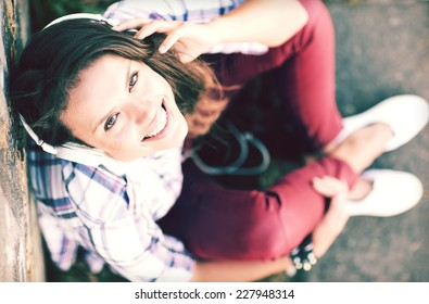 summer holidays and technology concept - teenage girl with headphones listening to music outside