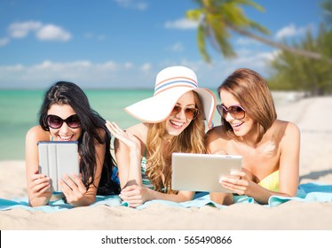 summer holidays, technology, people, travel and internet concept - happy young women in bikinis with tablet pc computers sunbathing over exotic tropical beach with palm trees and sea shore background