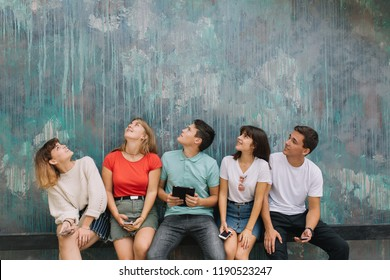 Summer holidays and teenage concept - group of smiling teenagers hanging out outside.