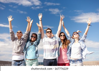 summer holidays and teenage concept - group of smiling teenagers in sunglasses holding hands up outside