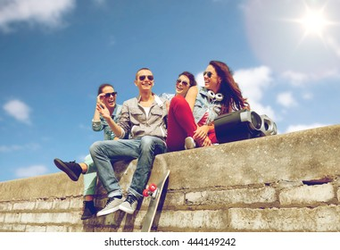 summer holidays and teenage concept - group of smiling teenagers with boob box and skateboard hanging out outside
