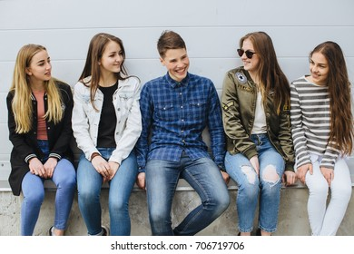Summer holidays and teenage concept - group of smiling teenagers with skateboard hanging out outside.