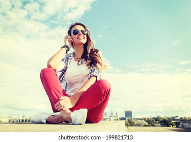 summer holidays and teenage concept - smiling teenage girl in sunglasses with headphones outdoors