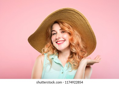 summer holidays and touring trips concept. young pretty woman in a big sunhat ready to go to the beach. cute stylish joyful girl portrait on pink background.