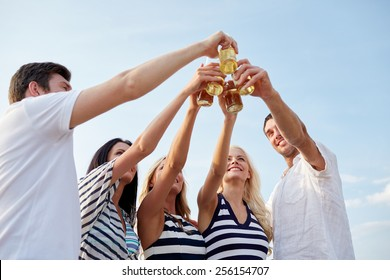 summer, holidays, tourism, drinks and people concept - group of smiling friends clinking bottles of beer or cider on beach