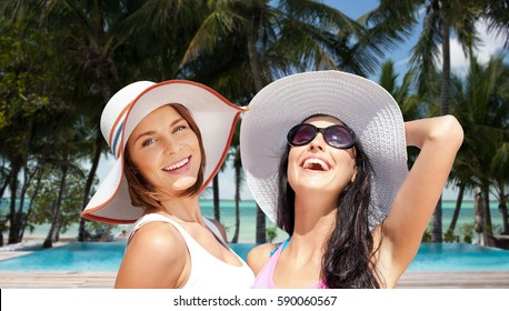 summer holidays, travel, people and vacation concept - happy young women in hats over exotic tropical beach with palm trees and pool background