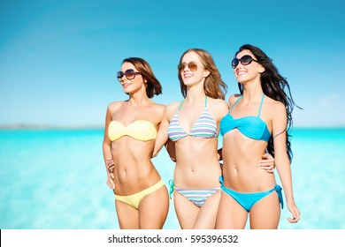 summer holidays, travel, people and vacation concept - happy young women in bikinis and shades over blue sky and sea background