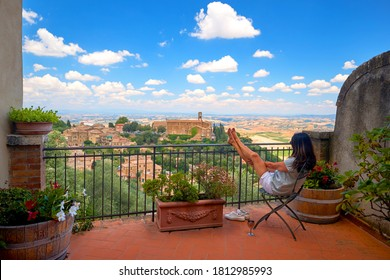 Summer Holidays in Tuscany. A middle-aged woman with long hair sitting in an armchair with her legs resting on a railing, watching city landscape from a terrace of a stone house. Montalcino, Italy.