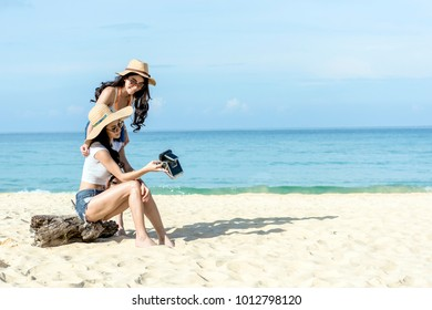 summer holidays, vacation and beach concept - girls taking selfie on the beach