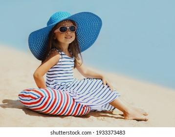 Summer holidays, vacation - beautiful little girl child wearing a straw hat, striped dress relaxing on beach near sea