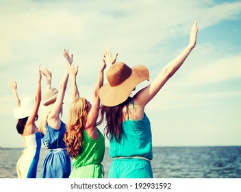 summer holidays and vacation - girls with hands up on the beach