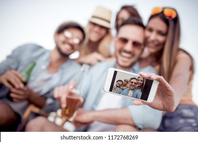 Summer, holidays, vacation and happiness concept - group of friends taking selfie with smart phone.