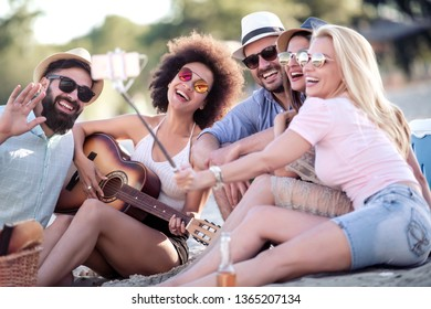 Summer, holidays, vacation and happiness concept-group of friends taking selfie with smart phone.