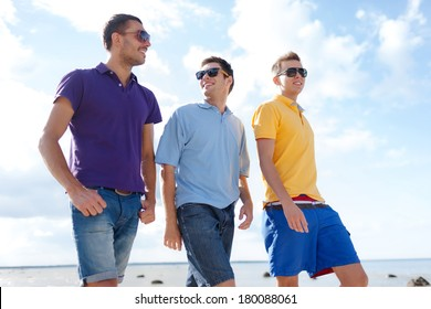 summer, holidays, vacation, happy people concept - group of male friends walking on the beach