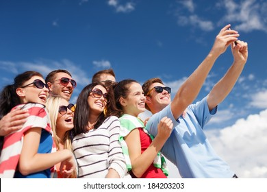summer, holidays, vacation, happy people concept - group of friends taking selfie with smartphone
