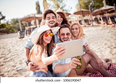 Summer holidays, vacation and people concept - group of friends taking selfie with tablet on the beach.