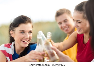 summer holidays, vacation, people and party concept - group of happy friends having fun and drinking non-alcoholic beer or soda lemonade on beach