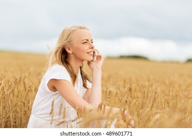 summer holidays, vacation, technology and people concept - smiling young woman in white dress calling on smartphone on cereal field