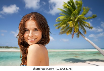 summer holidays, vacation and travel concept - happy young woman posing in bikini swimsuit over exotic tropical beach with palm tree background