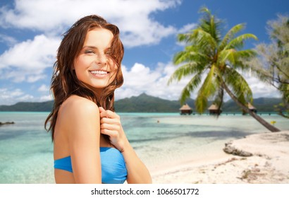 summer holidays, vacation and travel concept - happy young woman posing in bikini swimsuit over exotic tropical beach with bungalow sheds background