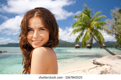 summer holidays, vacation and travel concept - happy young woman posing in bikini swimsuit over exotic tropical beach with bungalow sheds background in french polynesia