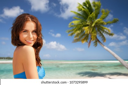 summer holidays, vacation and travel concept - happy young woman posing in bikini swimsuit over exotic tropical beach with palm tree background in french polynesia