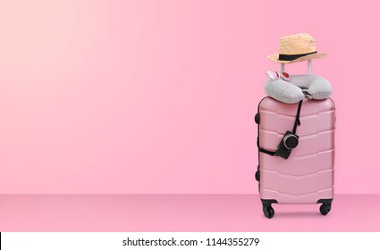 Summer holidays, vacation and travel concept. Suitcase or luggage bag with sun glasses, hat, pillow and camera on pastel pink background for copy space.