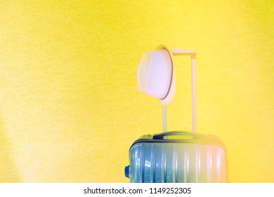 Summer holidays, vacation and travel concept. Suitcase or luggage bag with sun hat on yellow background sunflare toning