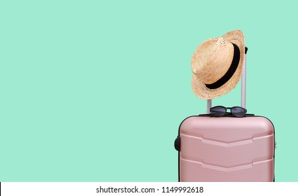 Summer holidays, vacation and travel concept. Suitcase or luggage bag with sun glasses and hat on pastel green background for copy space.