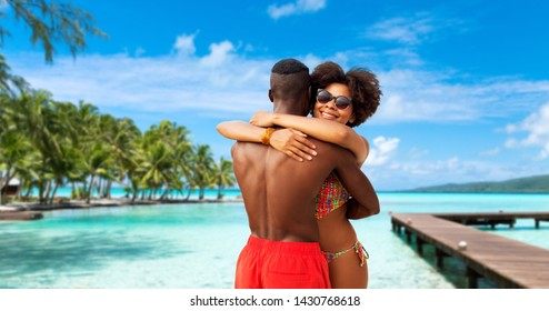 summer holidays, vacation and travel concept - happy african american couple hugging over tropical beach background in french polynesia