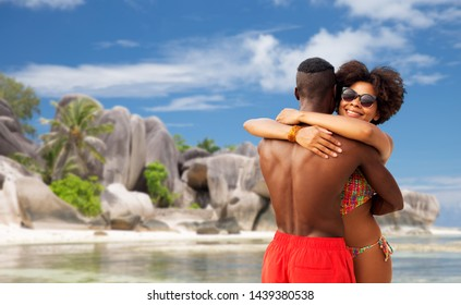 summer holidays, vacation and travel concept - happy african american couple hugging over tropical beach of seychelles island background
