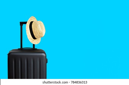 Summer holidays, vacation and travel concept. Suitcase or luggage bag with sun hat on blue background for copy space.