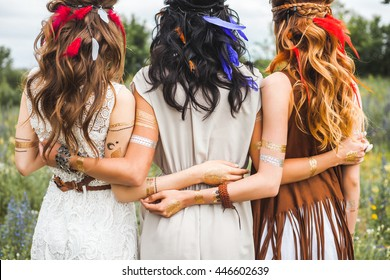 Summer holidays, vacation, travel and people concept - three beautiful hippie girl, photographed from behind, hairstyles, feathers, white dresses, flash tattoo, accessories, Bohemian, Bo-ho Style