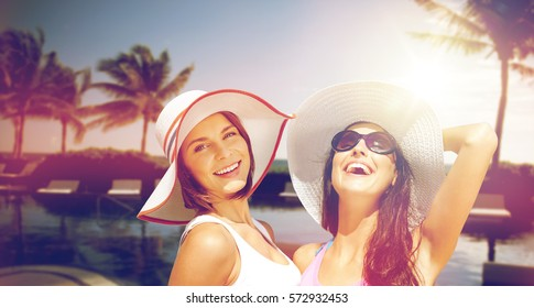 summer holidays, vacation, travel and people concept - smiling young women in hats and casual clothes on beach